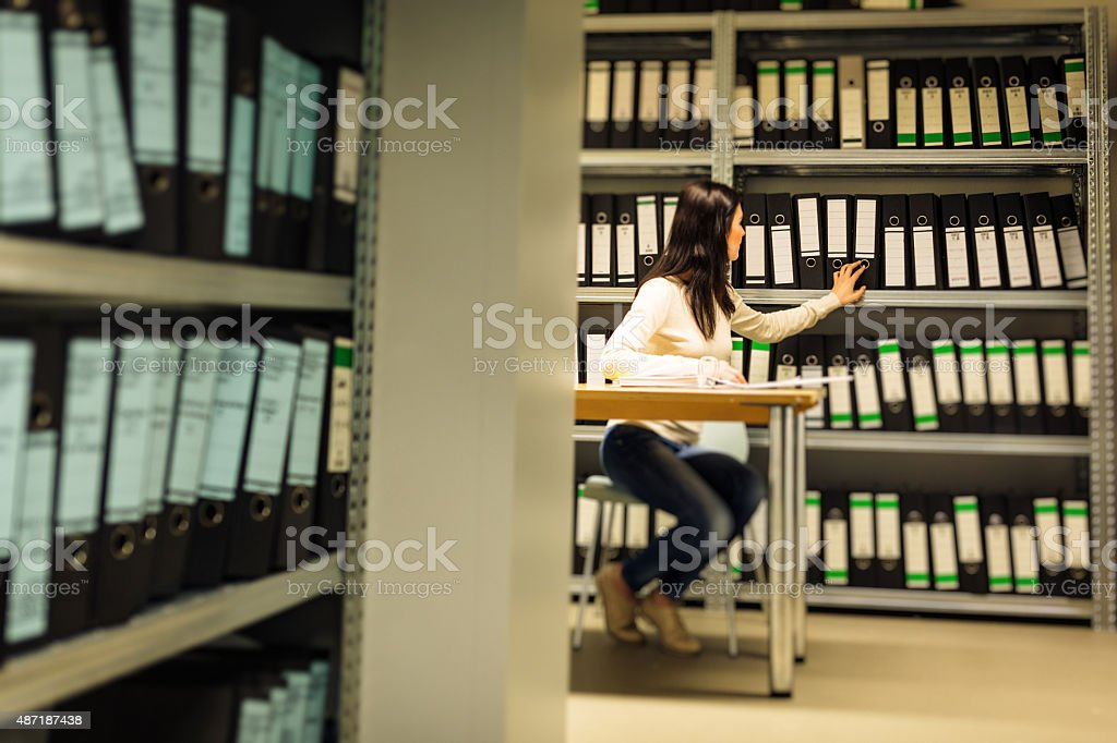 young woman checking documents in the archives stock photo