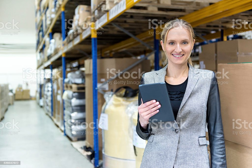 Young woman checking her deliveries in warehouse stock photo