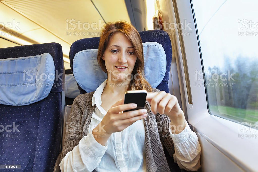 Young woman checking her smart phone on train stock photo