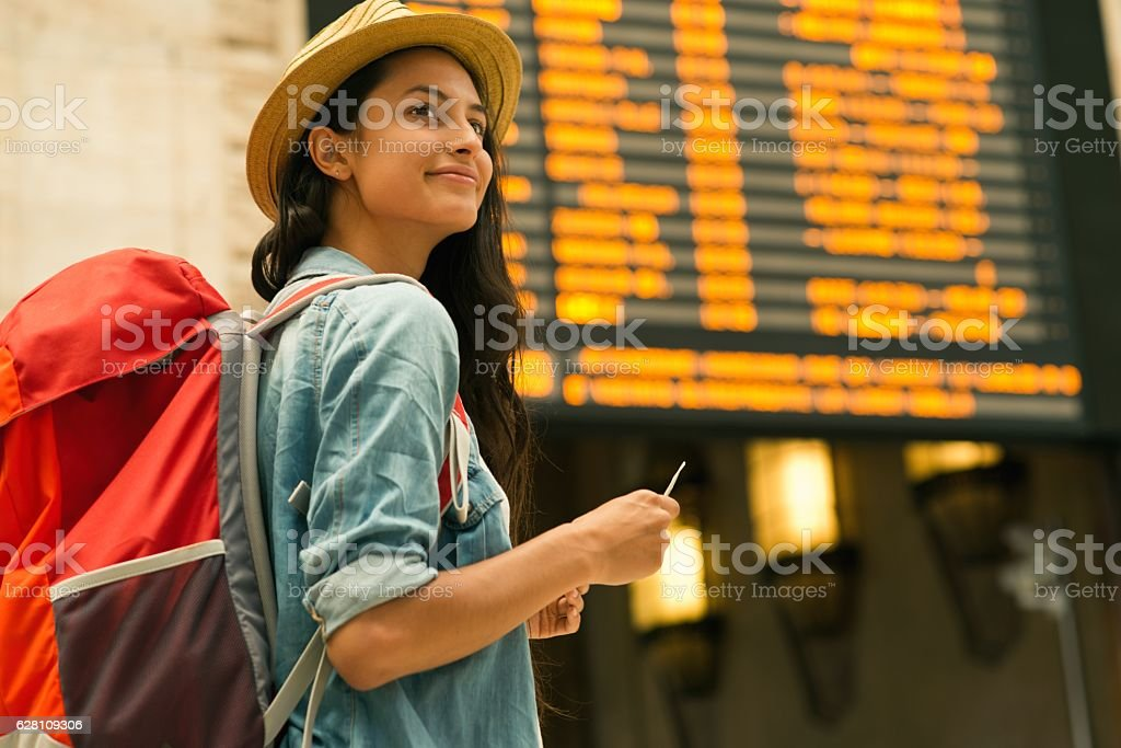 Young woman checking her train in time board stock photo