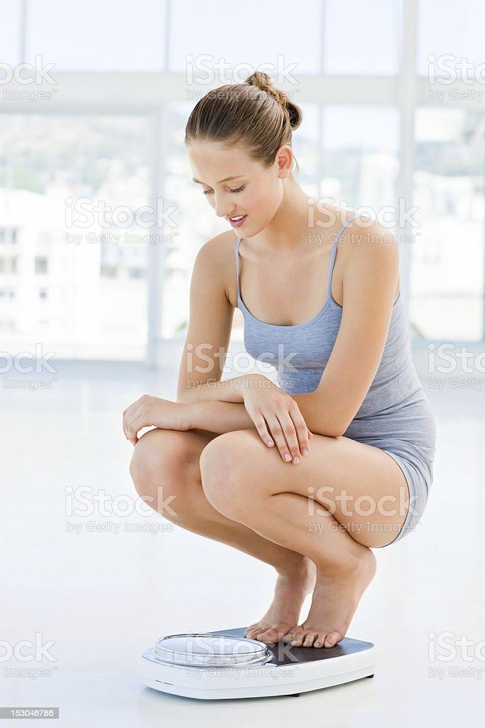 Young woman checking her weight royalty-free stock photo