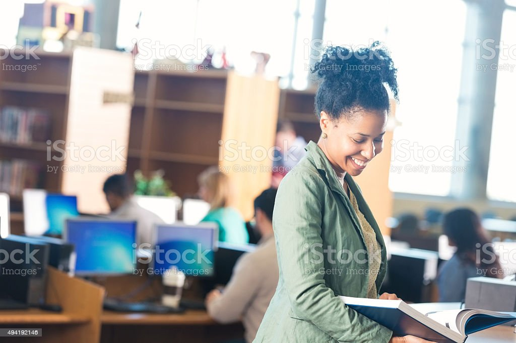 Young woman checking out book in college library stock photo