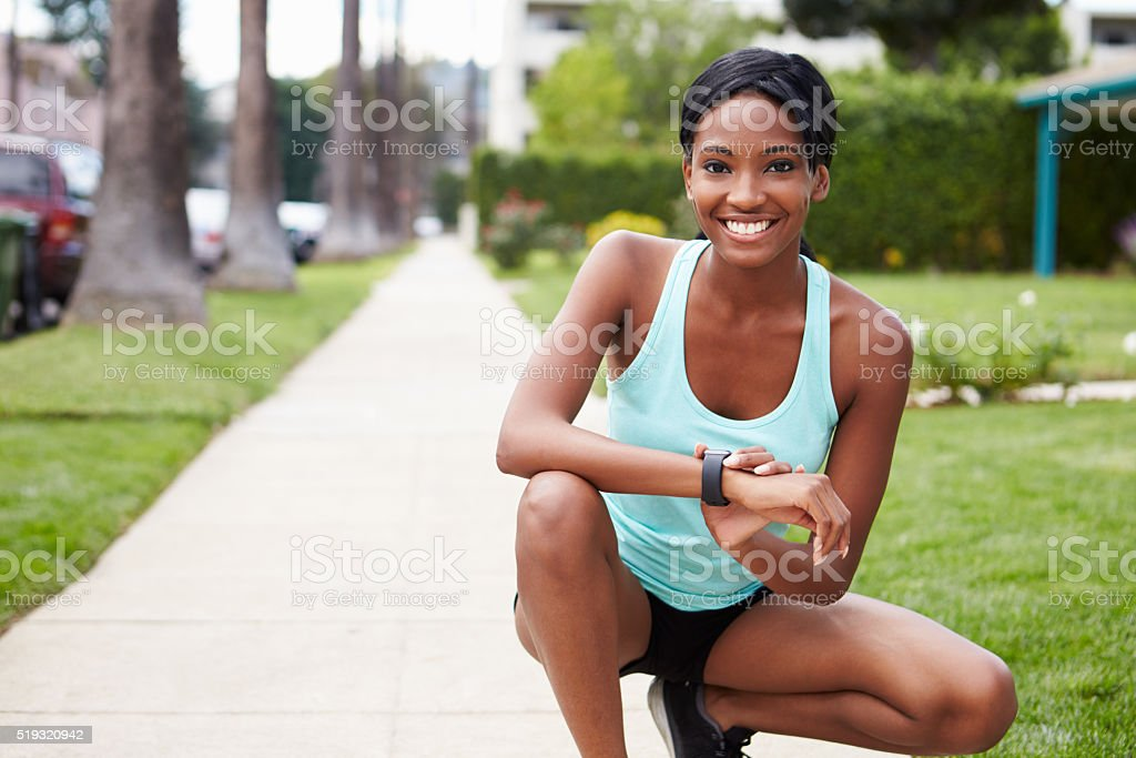 Young woman checking smart watch outdoors looks to camera stock photo