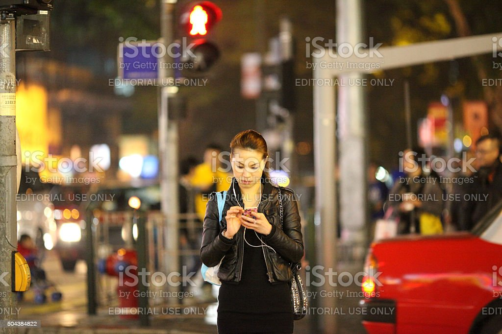 Young Woman Checking Smartphone in Hong Kong stock photo