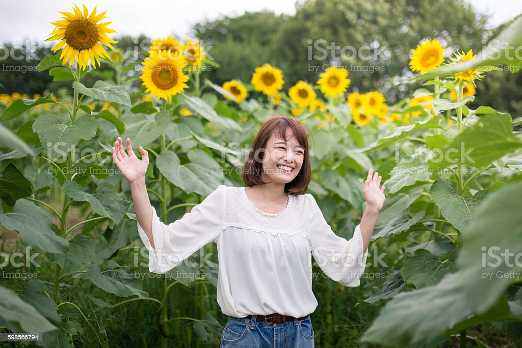 Young woman cheerfully smiling in sunflower field stock photo