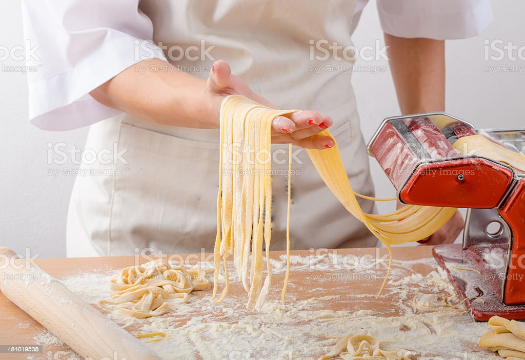 Young woman chef prepares homemade pasta stock photo