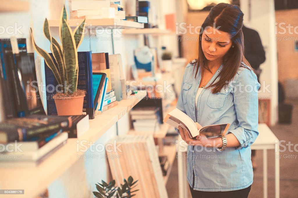 young woman choosing a book stock photo