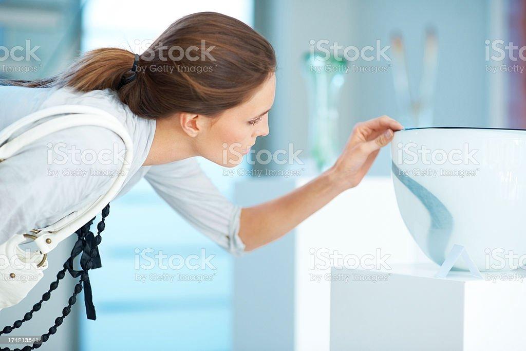 Young woman choosing a crockery in a shop stock photo