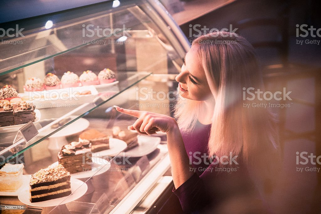 Young woman choosing a pastry in a bakery stock photo