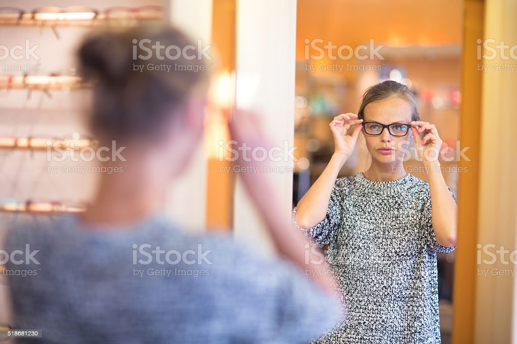 Young woman choosing new glasses stock photo