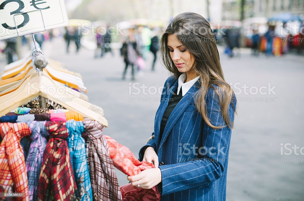 Young Woman Choosing Scarfs in a Street Shop stock photo