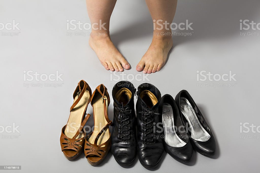 Young woman choosing which shoes to wear royalty-free stock photo