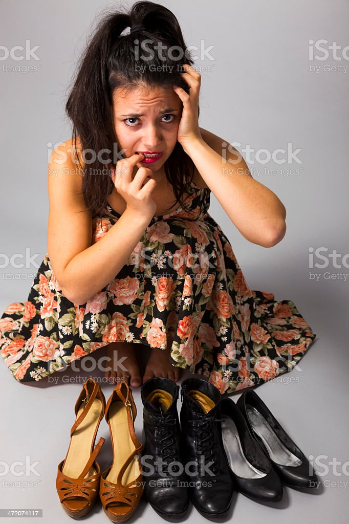 Young woman choosing which shoes to wear stock photo