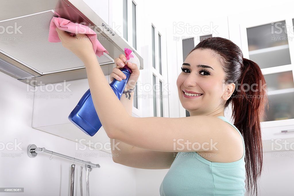 Young woman cleaning cooker hood stock photo