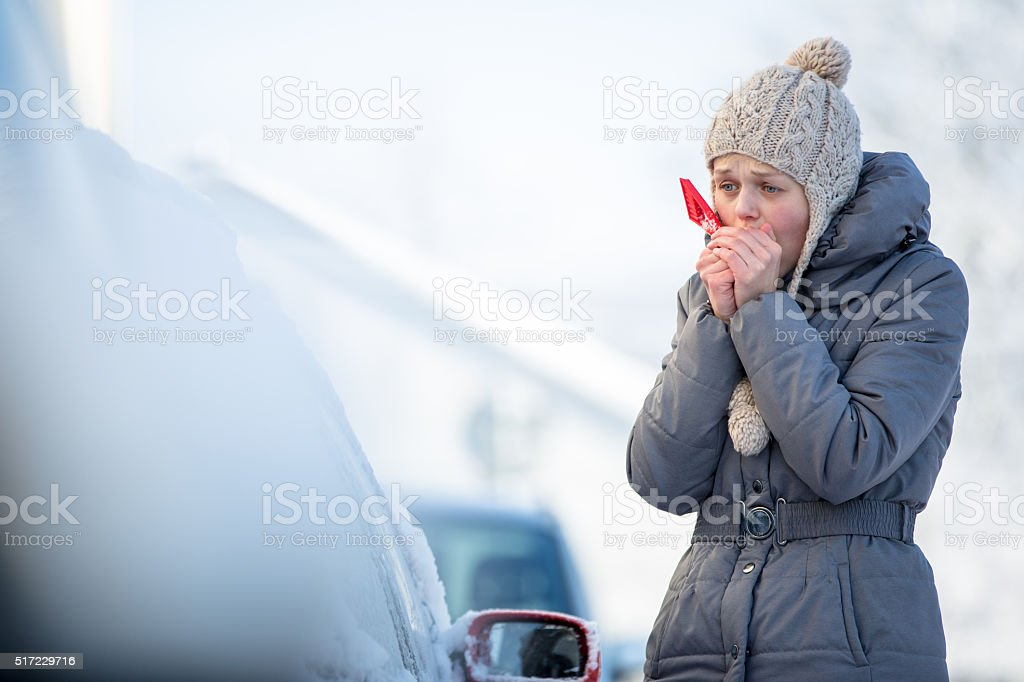 Young woman cleaning her car from snow stock photo