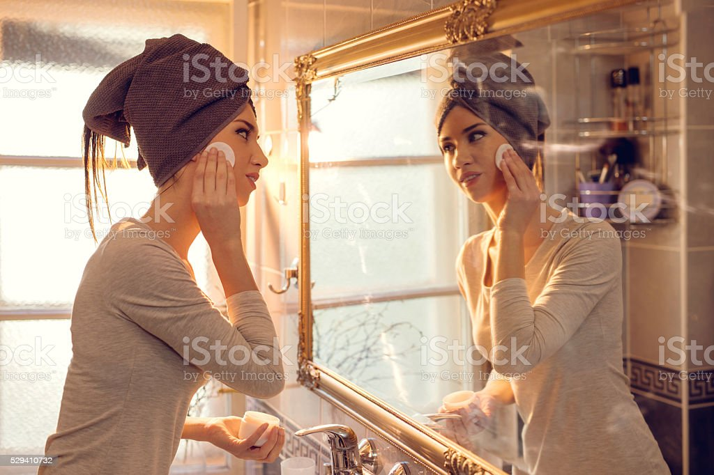 Young woman cleaning her face in the bathroom. stock photo