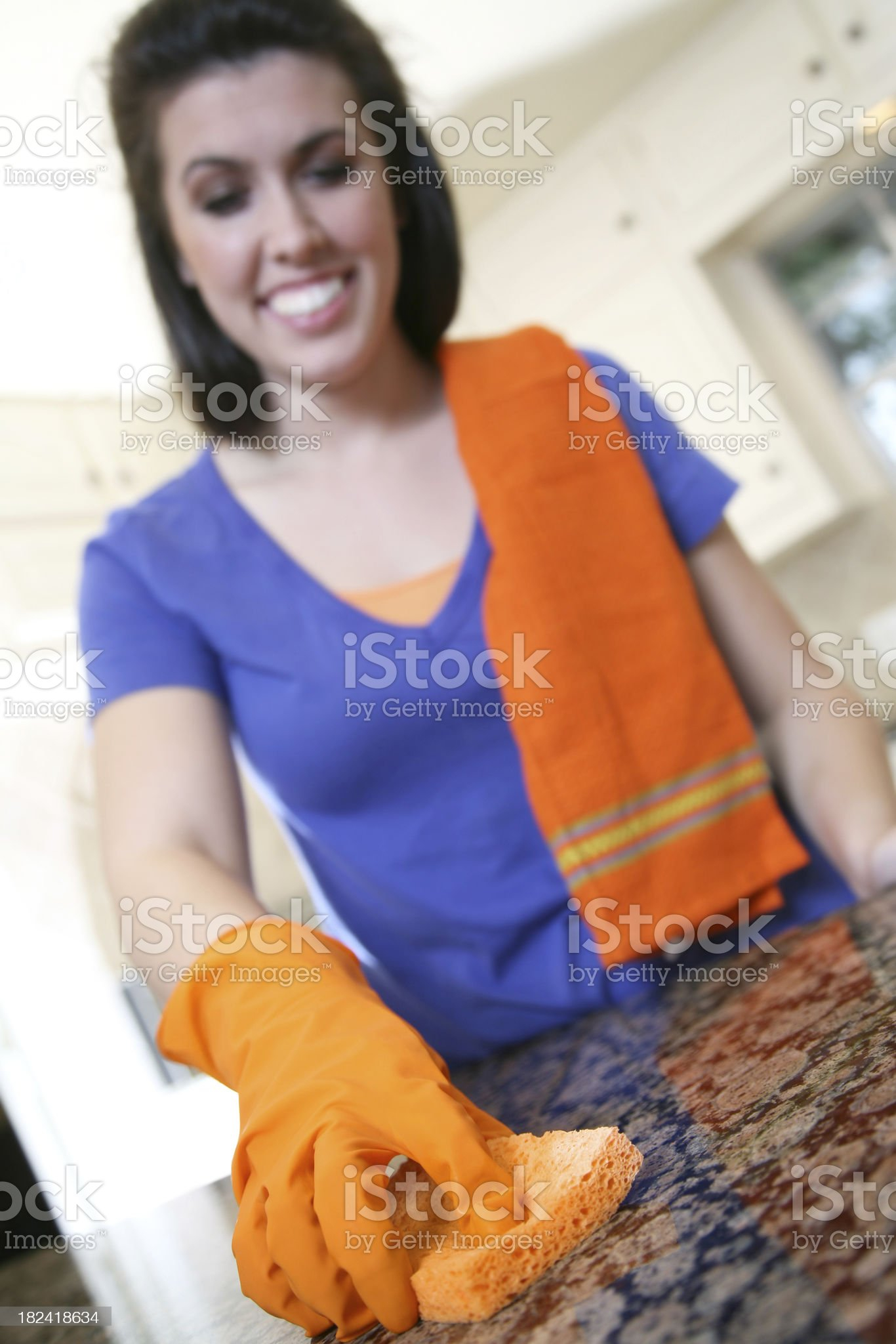 Young Woman Cleaning Her Kitchen Counter With Sponge royalty-free stock photo