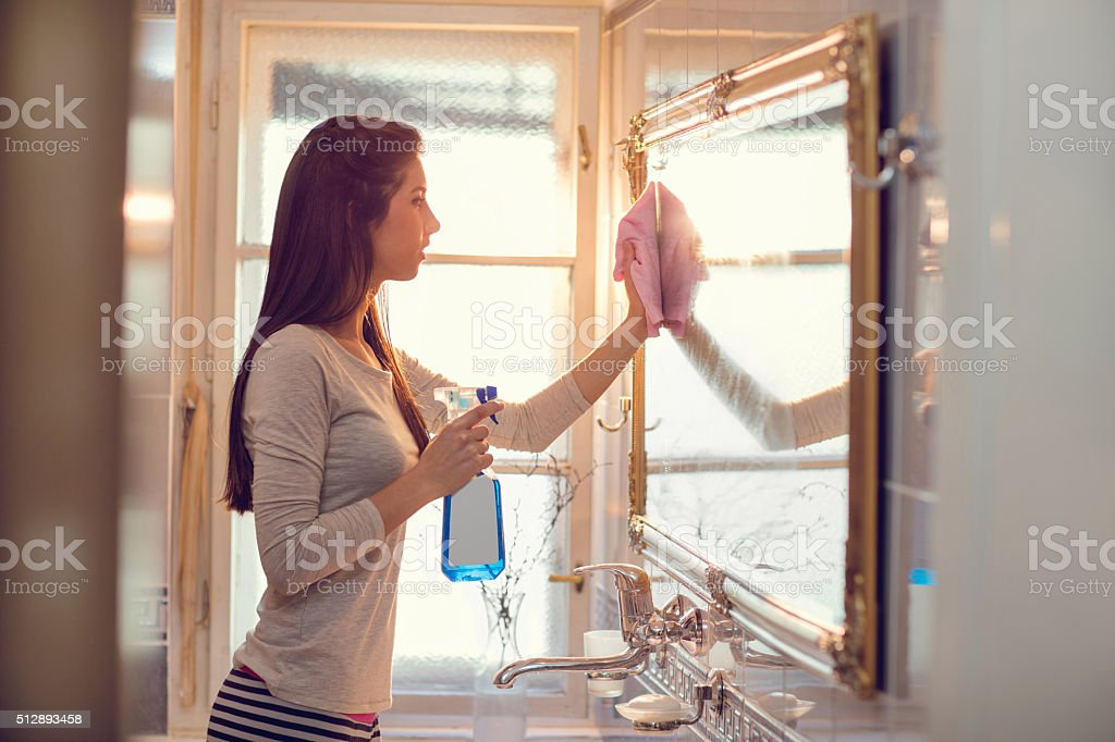 Young woman cleaning mirror in the bathroom. stock photo
