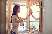 Young woman cleaning mirror in the bathroom.