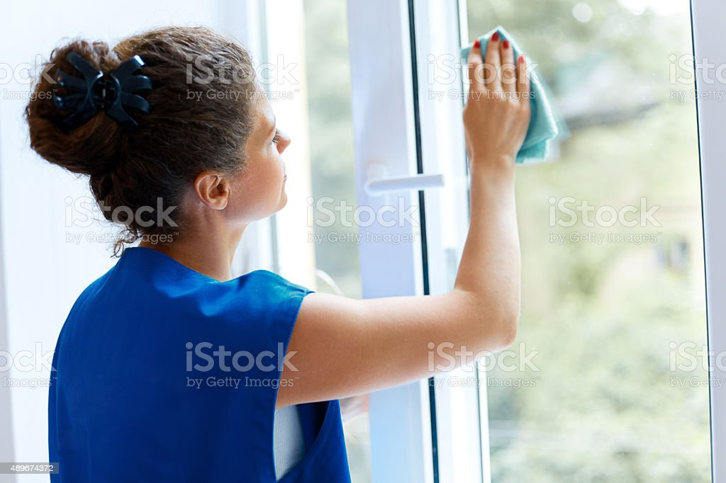 Young Woman cleaning window glass. Cleaning Company Worker stock photo