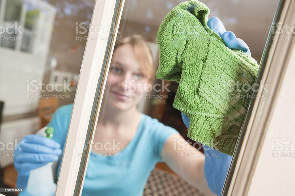 Young Woman Cleaning Window with Towel and Spray Detergent Product royalty-free stock photo