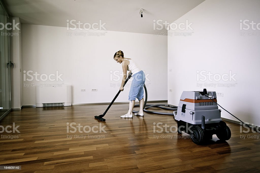 Young woman cleaning wooden floor royalty-free stock photo