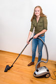 Young woman cleans floor with vacuum cleaner