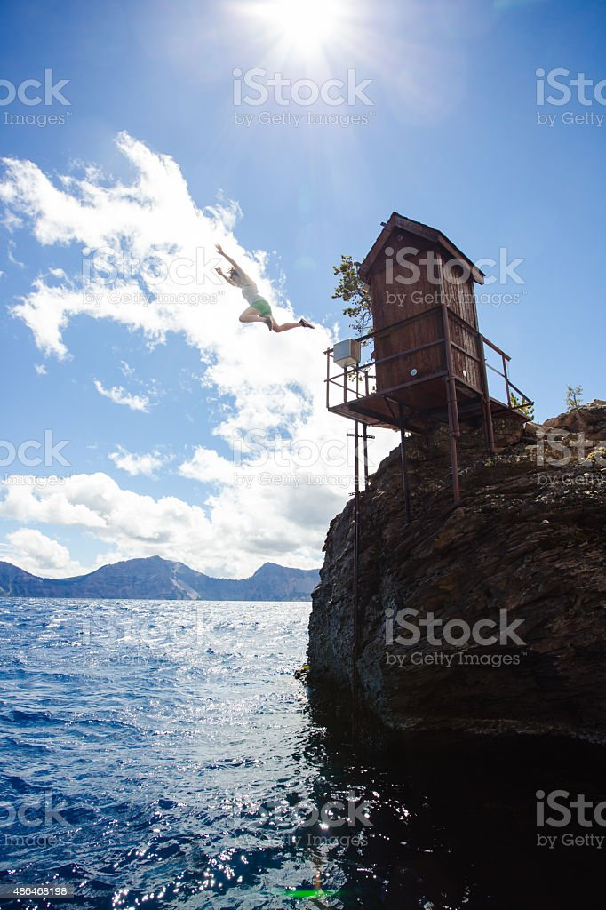 Young Woman Cliff Jumping Into Crater Lake stock photo