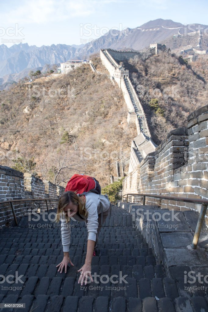 Young woman climbing the Great Wall of China stock photo