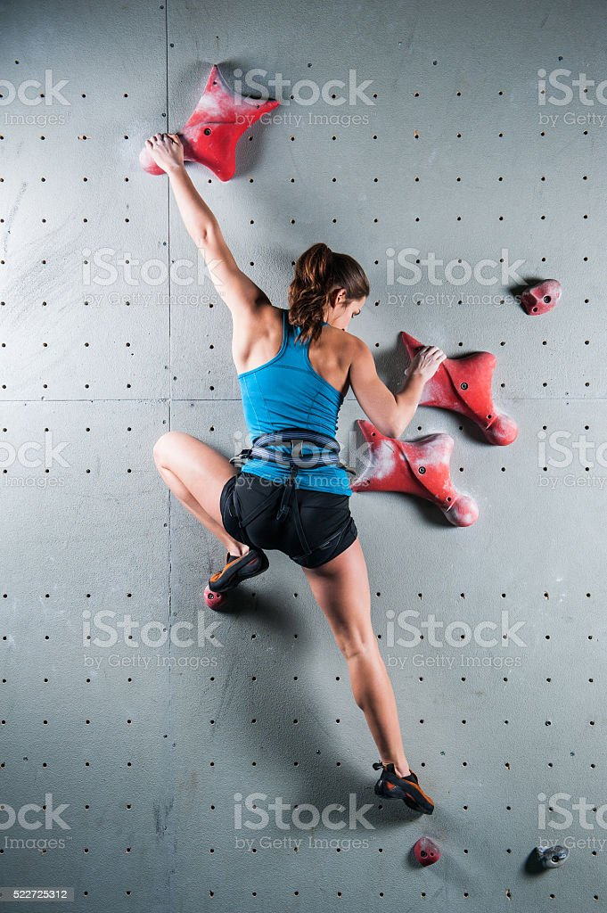 Young woman climbing up on practice wall in gym stock photo