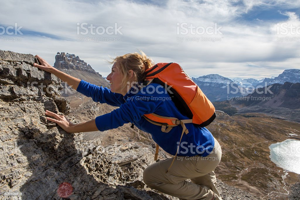 Young woman climbs steep rock to reach mountain top stock photo