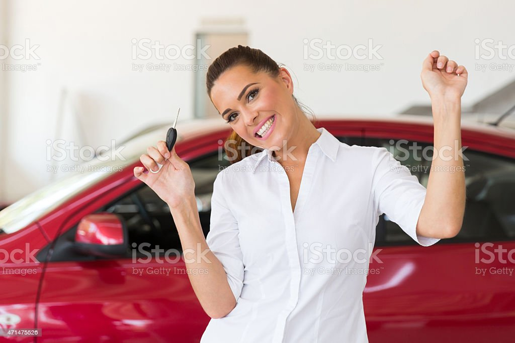 young woman collecting her new car from dealership stock photo