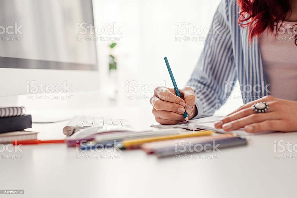 Young woman coloring adult coloring book stock photo