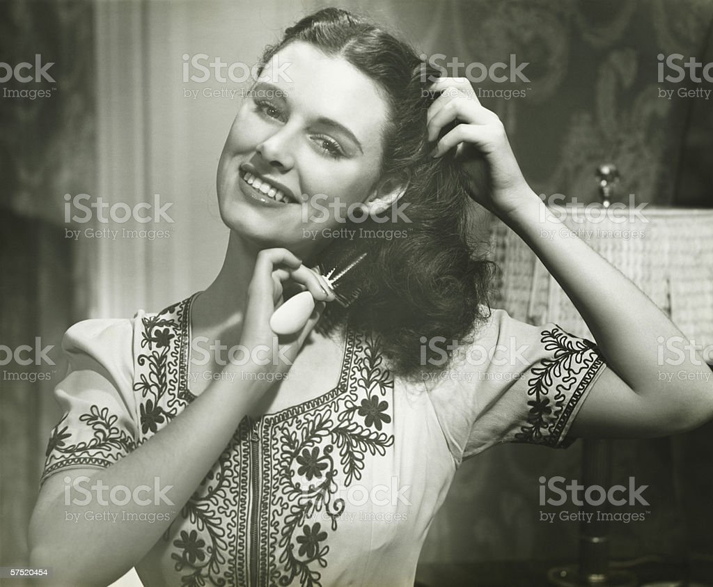 Young woman combing hair, (B&W), portrait stock photo