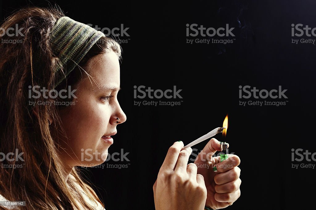 Young woman concentrating on lighting marijuana joint stock photo