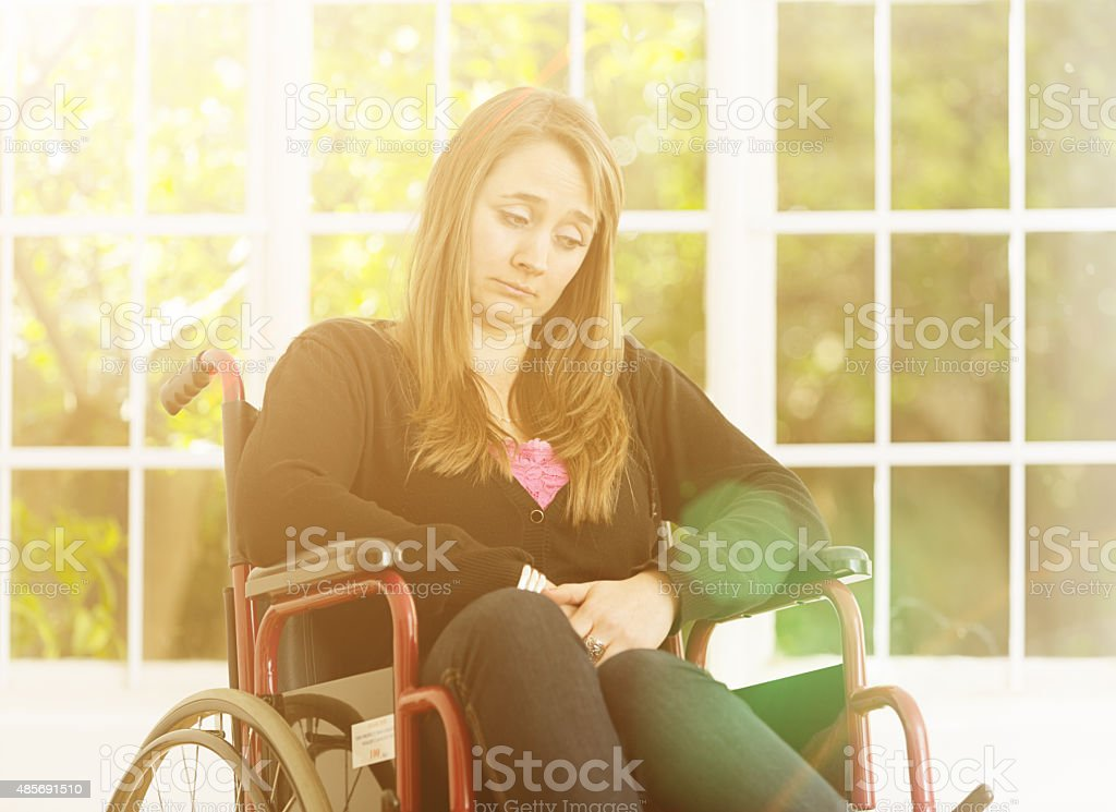Young woman confined to wheelchair looks sad and depressed stock photo