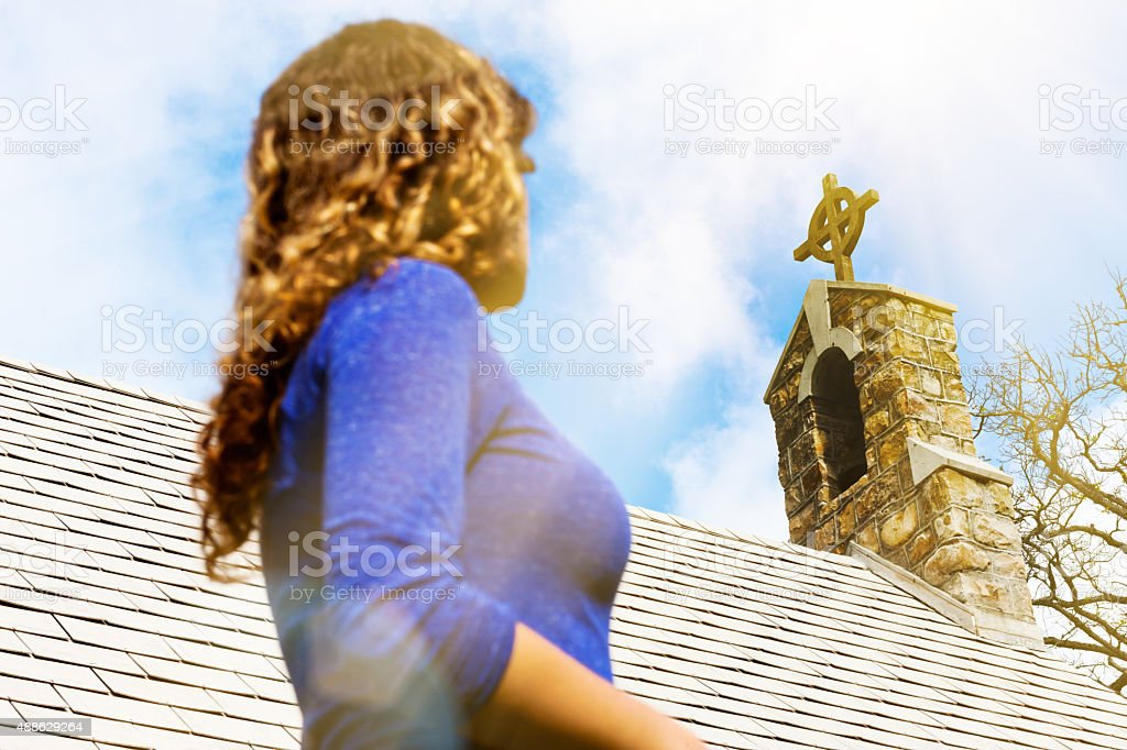 Young woman contemplates Christianity, looking up at church steeple stock photo
