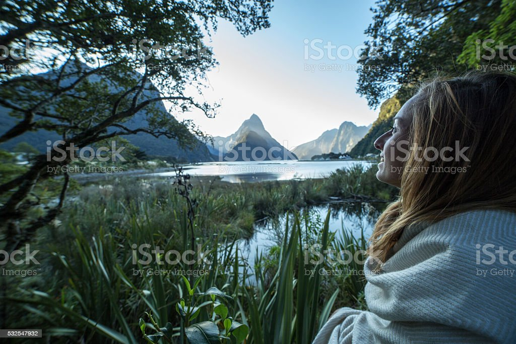 Young woman contemplating the beauty of nature, Milford Sound stock photo