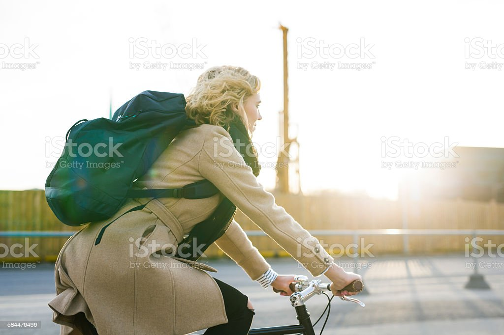 Young Woman Contemplating While Riding Bicycle In The Evening stock photo