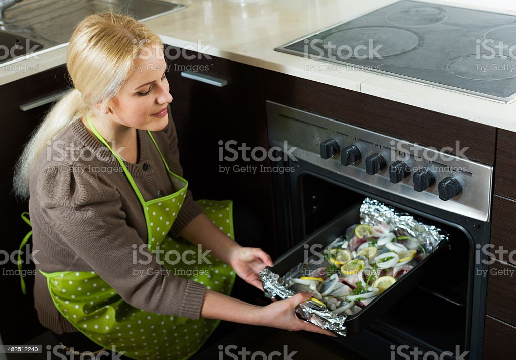 Young woman cooking fish stock photo