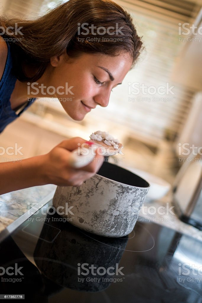 Young woman cooking rice in the kitchen. stock photo