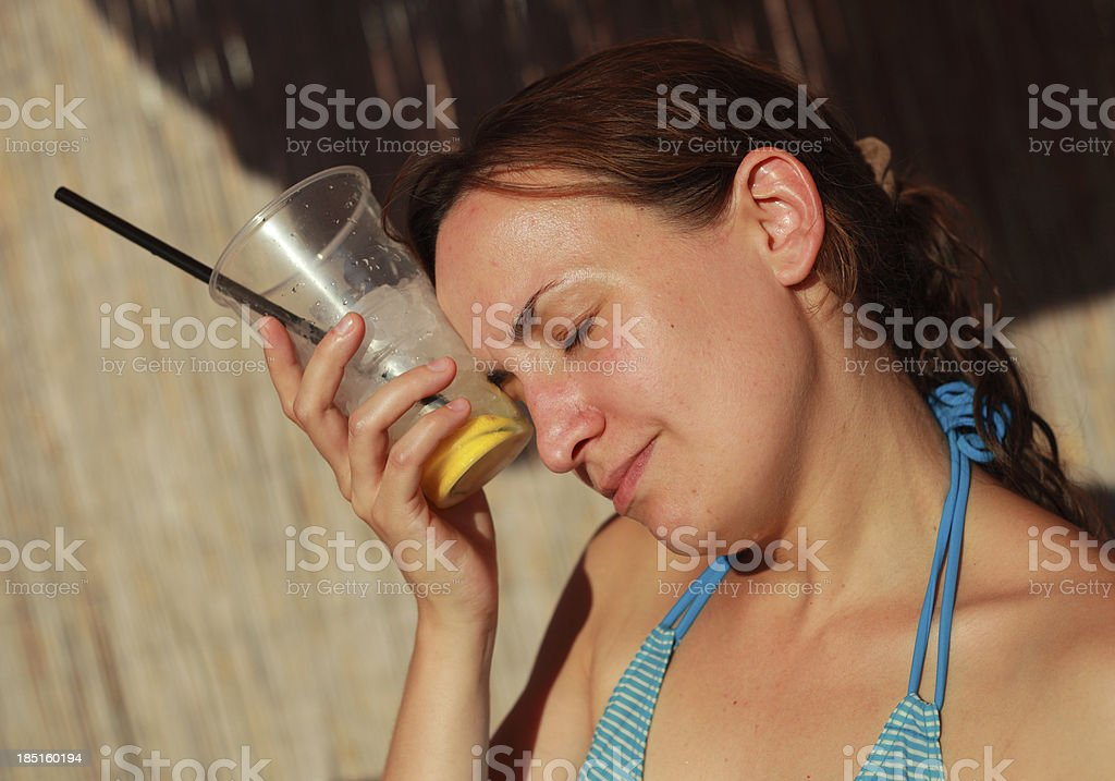 Young woman cooling herself with cocktail stock photo
