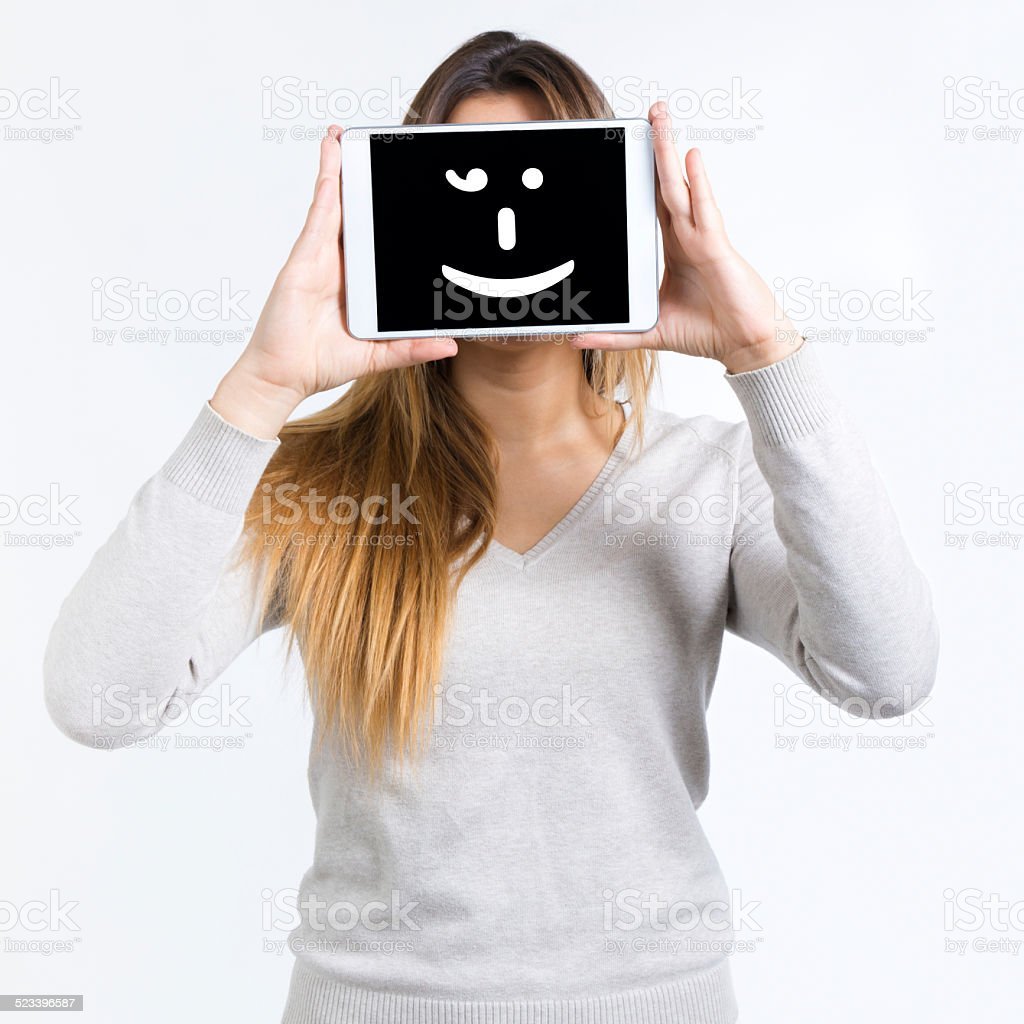 Young woman cover her face with digital tablet. Isolated. stock photo