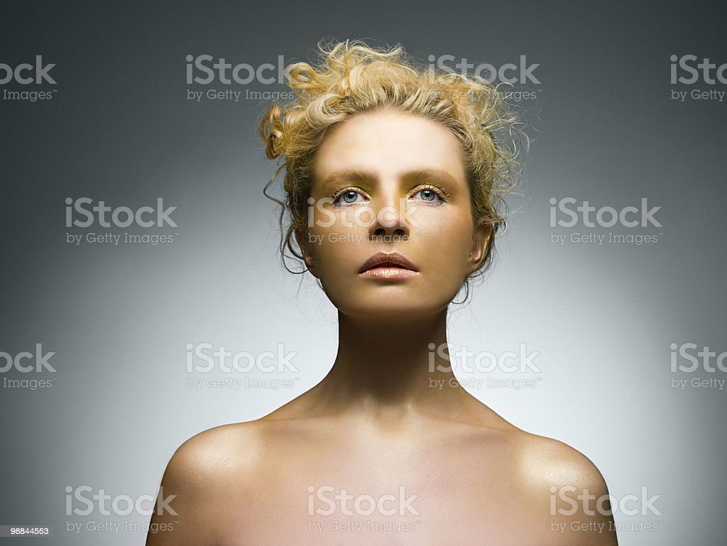 Young woman covered in gold make up stock photo