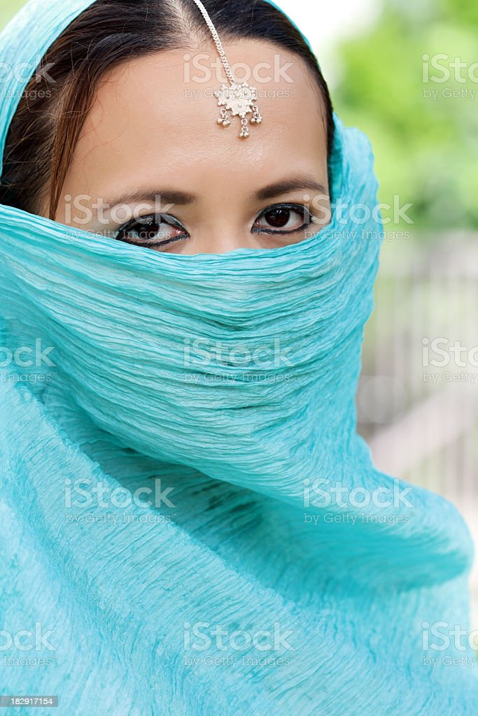 Junge Frau, die mit einem blauen Schleier Blick in die Kamera Lizenzfreies stock-foto