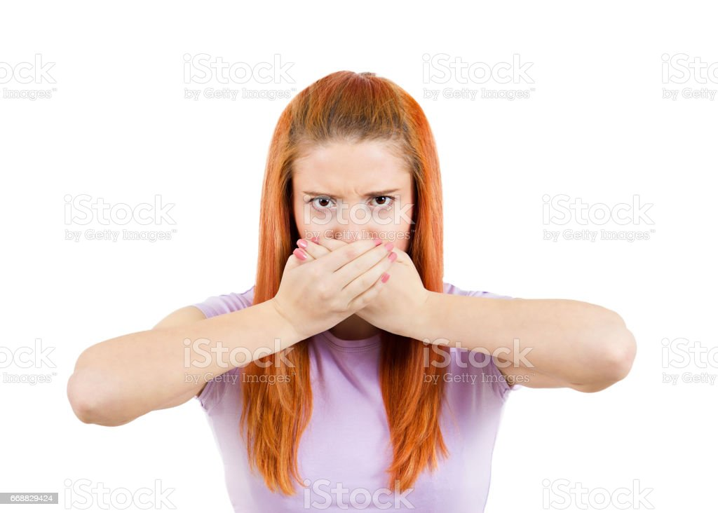 young woman covering closed mouth. Looking unhappy stock photo