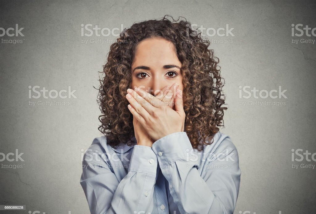 young woman covering closed mouth with hands. stock photo