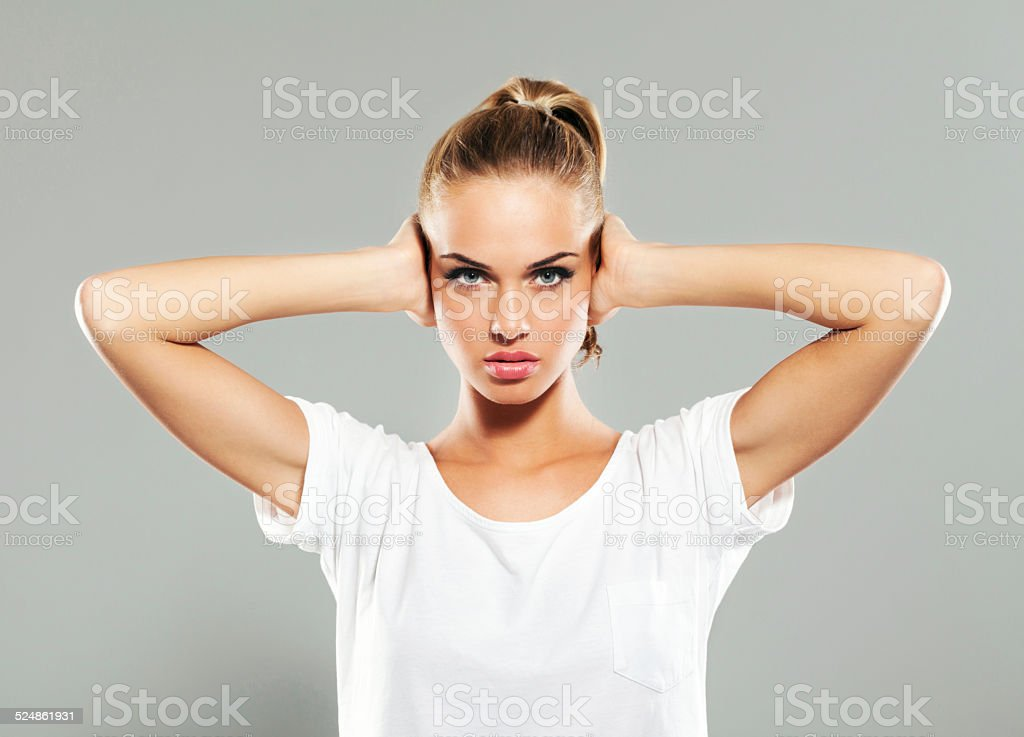 Young woman covering ears with hands stock photo