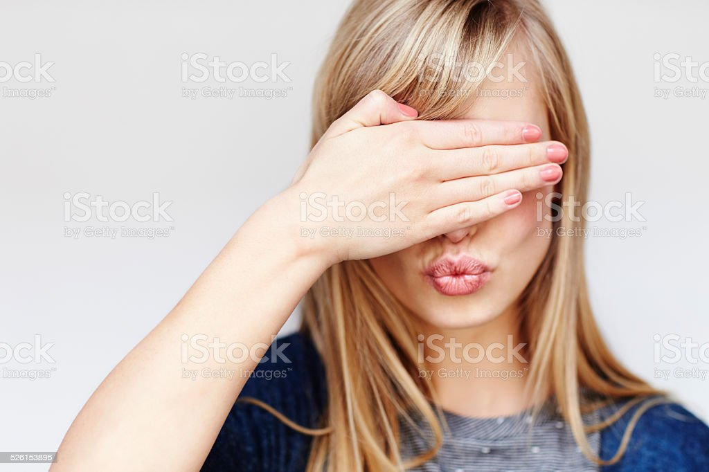 Young woman covering eyes and blowing kiss stock photo