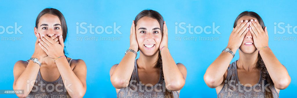 Young woman covering eyes, ears and mouth with her hands stock photo
